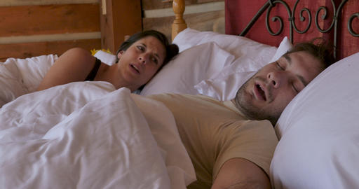 Young woman shaking a snoring man sleeping next to her in bed during the morning trying to wake him Live Action