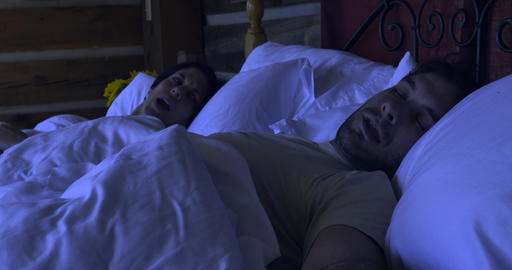 Woman unable to wake up a man lying in bed shaking him hard while he is unresponsive at night Live Action