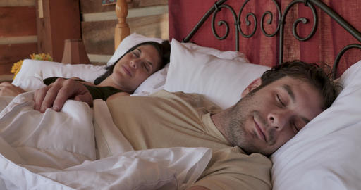 Happy attractive young couple in their early 30s or late 20s getting a good nights sleep smiling and Footage