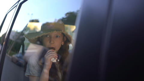 little pretty girl eating chocolate donuts in car backseat. road trip concept Footage
