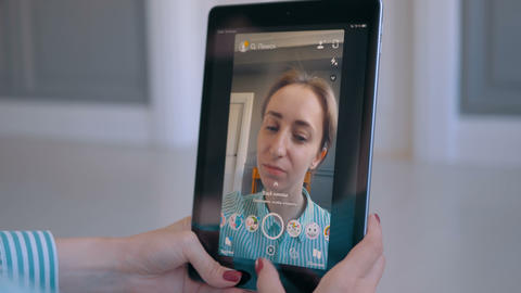 Woman using Snapchat multimedia messaging app with face mask on smartphone GIF