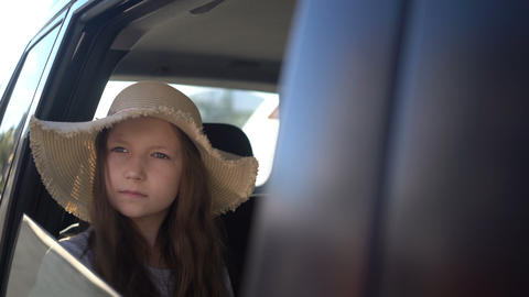 Happy beautiful girl with straw hat traveling in a car backseat. road trip Footage