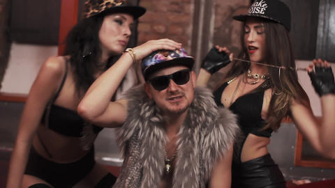 Rich rapper man in fur vest with sexy girls stsitting on bed rapping Live Action