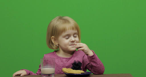 Girl sitting at the table and eating chocolate, cookies and drinks cacao Live Action