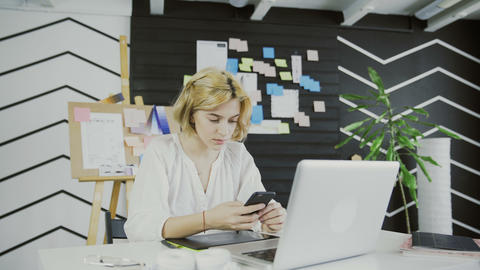 Attractive female designer using smart phone in the office Footage