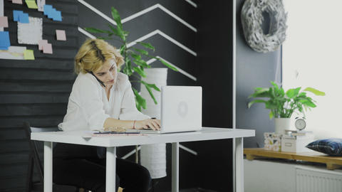 Busy business woman talking on cell phone and working on computer in office Live Action