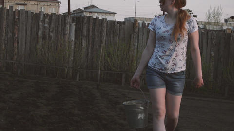 Girl in the garden planting potatoes at sunset Stock Video Footage