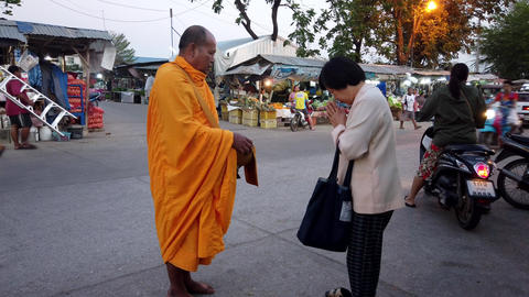 Sukhothai, Thailand - 2019-03-06 - Monk Blesses Woman in Market Footage
