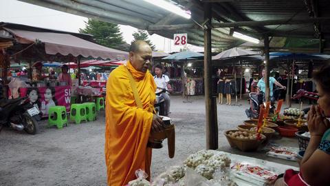 Sukhothai, Thailand - 2019-03-06 - Monk Blesses Woman Vendor in Market Footage