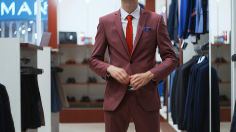 Young man try on classical suit in the suit shop Footage
