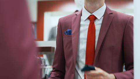 Male dressed in elegant red suit chooses his tie Footage