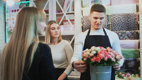 Young cheerful man and beautiful woman florists are talking to customer and Live Action