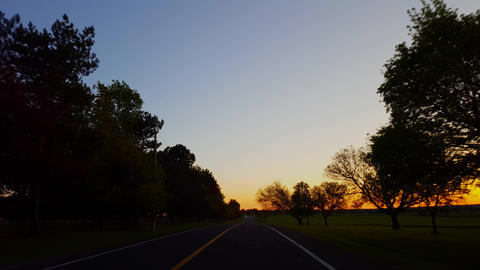 Driving Rural Countryside Road During Sunset. Driver Point of View POV While Sun Rises on Horizon Footage