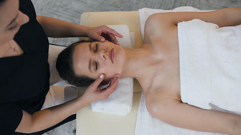 Young caucasian woman having treatment massage on the face in the massage salon Footage