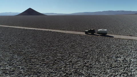 Aerial drone scene following from the side a 4x4 with caravan traveling off road on wide salar with Footage