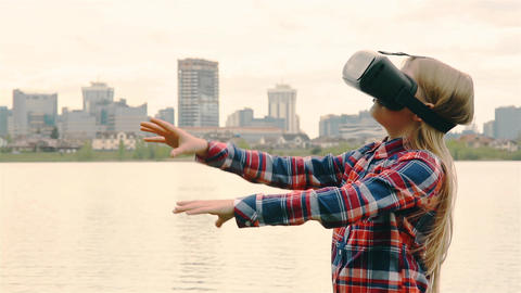 Blonde girl with a VR headset on the background of a big city near sea HD 1920 Footage