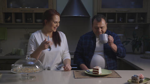 Female and male confectioner chef cook healthy organic cupcakes tasting a slice Footage