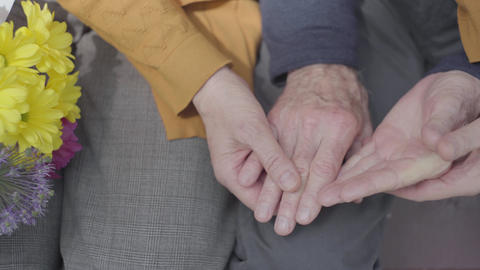 Closeup hands of an old woman holding the hand of old man. Hands of mature Live Action