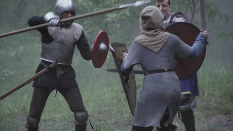 Fight on the battlefield, people in armor are fighting with swords Live Action