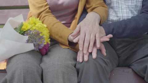 Close up hands of an old woman holding the hand of old man. Hands of mature Live Action