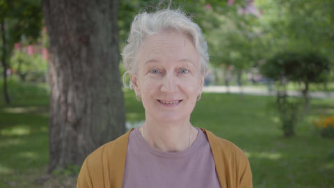 Different emotions of old woman with grey hair in the beautiful park. Adorable Live Action
