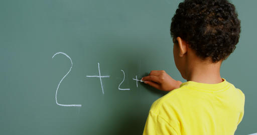 Rear view of African American schoolboy solving math problem on chalkboard in classroom at school 4k Live Action
