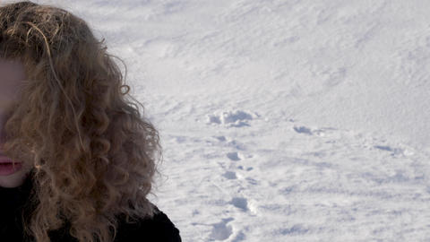 Beautiful young woman with curly hair in background of winter snow Steam from Footage