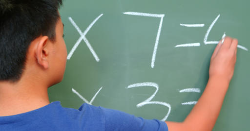 Rear view of Asian schoolboy solving math problem on chalkboard in classroom at school 4k Live Action