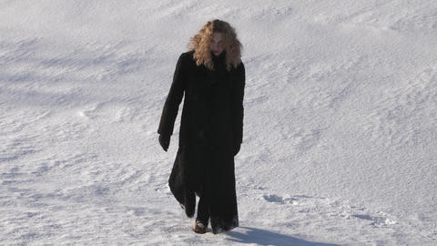 Hard steps thru the snow fields of Beautiful young woman with curly hair Footage
