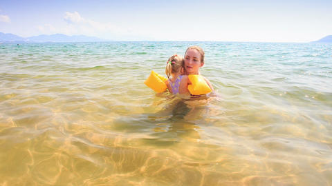 Blond Mother Holds in Arms Little Daughter in Azure Sea Stock Video Footage