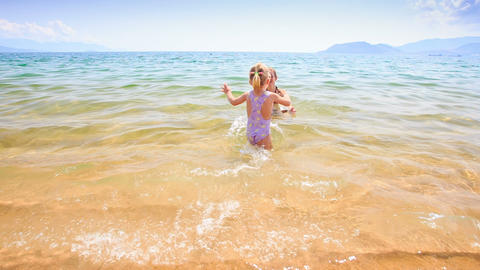 Little Girl Walks in Shallow Water to Mother in Azure Sea Footage