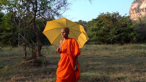 Haberna, Sri Lanka- 2019-03-22 - Young Monk Walks Across Field With Yellow Footage
