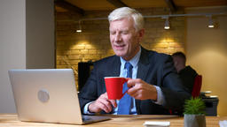 Closeup shoot of old caucasian employee using the laptop and drinking coffee Footage