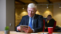 Closeup shoot of old caucasian businessman browsing on the tablet indoors in the Footage