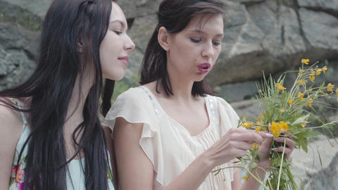 Two beautiful women with black hair braid flower crown near huge stone with Footage