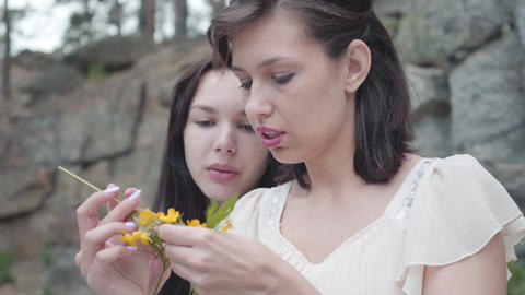 Portrait two beautiful women with black hair braid flower crown near huge stone Live Action