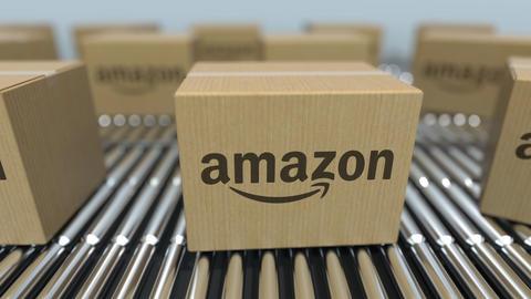 Carton boxes with Amazon logo move on roller conveyor. Conceptual editorial Live Action