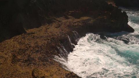 Ocean water breaks on rocks on bright sunny day Footage