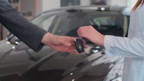 Happy man receiving keys to his new bought car with professional car dealer at Footage