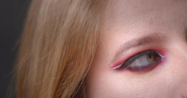 One eye shoot of blonde model with bright make-up blinks into camera watching Footage