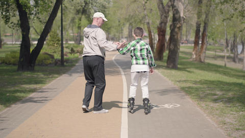 Grandfather teaches his grandson to roller skate in the park. Leisure outdoors Footage
