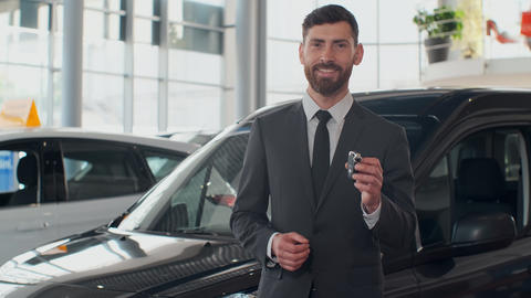 Professional car salesman smiling happily holding car keys standing in front of Live Action