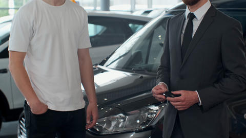 Man hand gives a car keys to male hand in the car dealership close up Footage