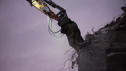 Demolition Excavator Arm Chipping Wall Debris with Purple Sky Background Live Action