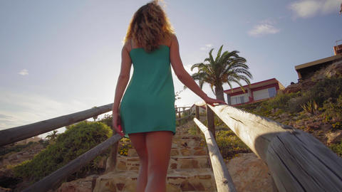 Back view. Young woman go from the beach climbing up the stairs. A woman walk up Footage