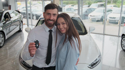 Visiting car dealership. Beautiful couple is holding a key of their new car Footage