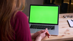 Rear portrait of businesswoman sitting in front of laptop with green chroma Footage