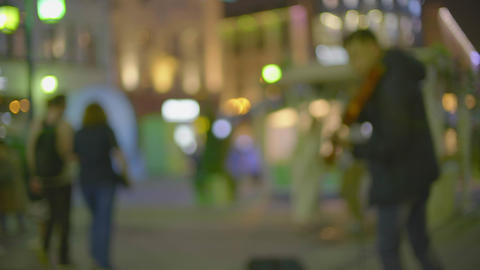 Blurred street musician plays electric violin on illuminated pedestrian street Live Action
