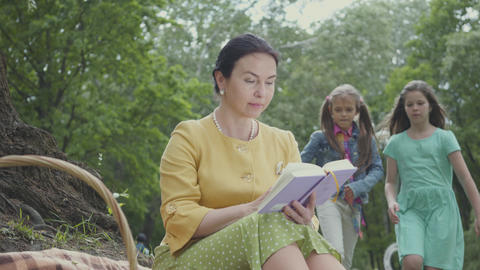 Elegant senior woman sitting on the blanket under the tree in the park reading Footage