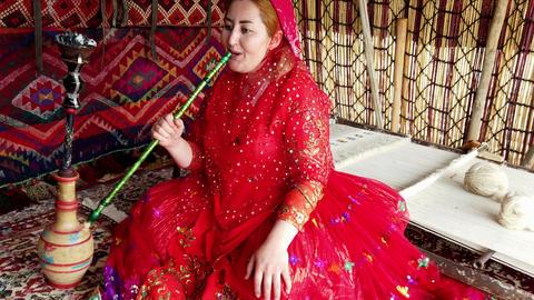 Shiraz, Iran - 2019-04-09 - Qashqai Woman in Red Dress Smokes Water Pipe Closeup Footage